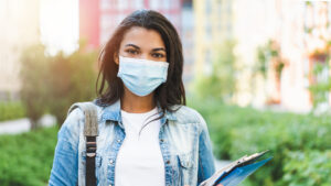 Female student walking to class wearing a surgical mask